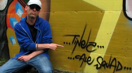 """Simone """"Tinez"""" Martinelli, grafitti artist, poses in front of his work."""