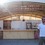 Director of the Festival in Cagli, Luca Ascani, stands in front of a beer kiosk.