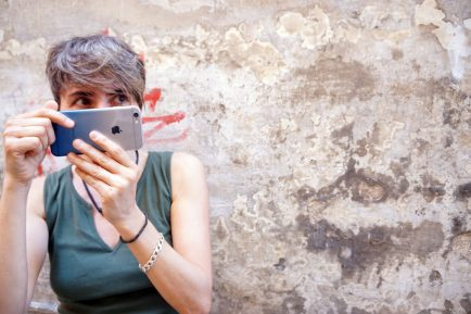 Photographer Samantha Gazzetta peeks behind her iPhone outside her shop in Cagli. Photo by Aimee Elber / Gonzaga in Cagli