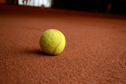 Tennis balls skid and collect dust from the red clay surface of the court.