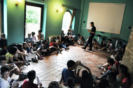 Children listen to Father Diego Fascinetti during summer camp.