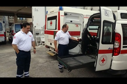 Filippo Torri and Marco Pedando demonstrate the ramp used to transport wheelchair patients.