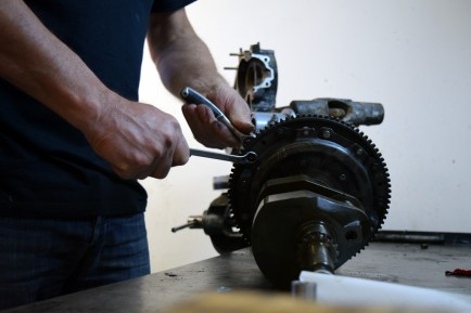 With wrenches in hand, Roberto disassembles a motorcycle engine.